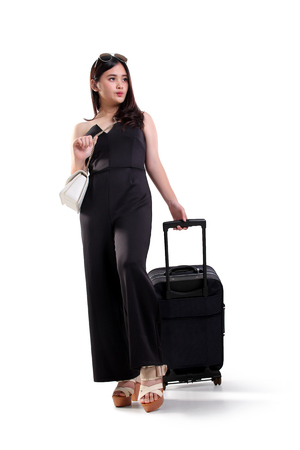 Full length portrait of attractive Asian woman walking with travel bag and looking sideways, isolated on white background