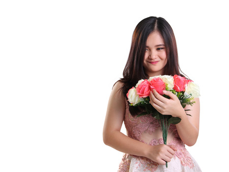 blushing: Cute shy Asian girl holding a bunch of roses with blushing face, isolated on white background for copy space Stock Photo
