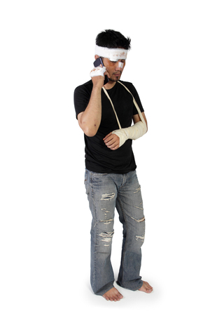 beaten up: Full body shot of a man with broken arm and beaten up face making phone call, isolated on white background