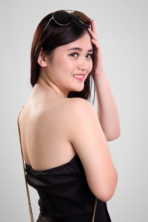 bikini top: Closeup portrait of beautiful Asian girl in summer dress looking back and smiles