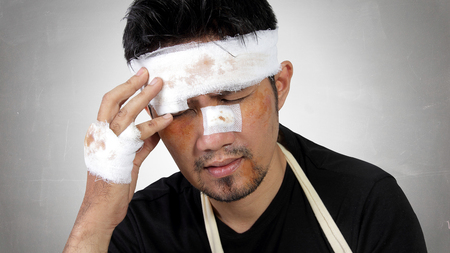 head pain: Close up expression of a man with bruised and bandaged face feels traumatic head pain. Conceptual image of accident victim healthcare Stock Photo
