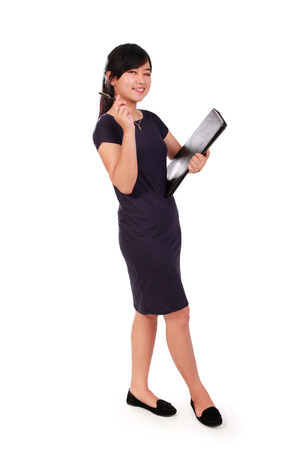 full shot: Full length shot of cheerful female Asian office worker posing with document keeper, isolated on white background