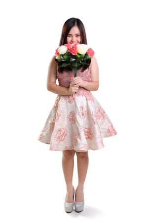 prom queen: Full length portrait of shy teenage girl smiling and covering her face with flowers, isolated on white background