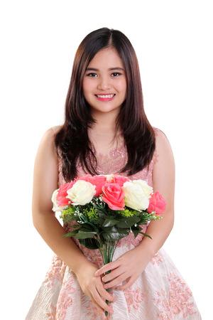 白い背景に分離されたバラの花束を持って幸せな美しいアジア 10 代の少女の肖像画
