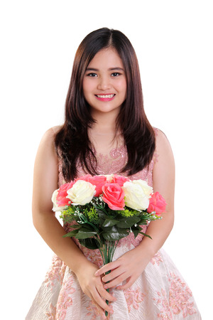 Portrait of happy beautiful Asian teenage girl holding a bouquet of roses, isolated on white background Stok Fotoğraf
