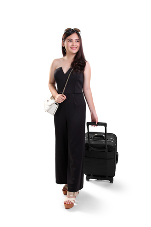 business traveller: Full length portrait of beautiful young Asian woman smling while traveling with suitcase, isolated on white background