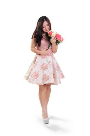full shot: Full length shot of cheerful Asian teenage girl walking while holding a bunch of roses, isolated on white background Stock Photo