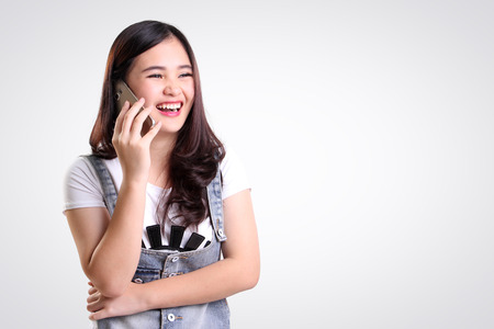chit chat: Cheerful Asian teenage girl laughing while talking on cellphone, on white background for copy space