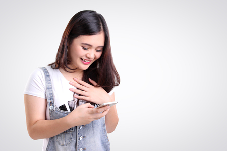Attractive Asian teenage girl looking at her mobile phone screen with joyful face, on white background for copy space Archivio Fotografico