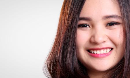 コピー スペースと白い背景で隔離のカメラに笑顔かわいいアジアの十代の少女の顔を閉じる