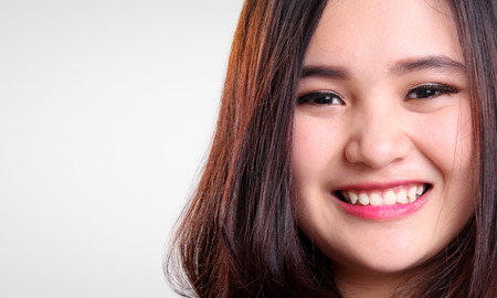 Close up face of cute Asian teenage girl  smiling to camera, isolated on white background with copy space
