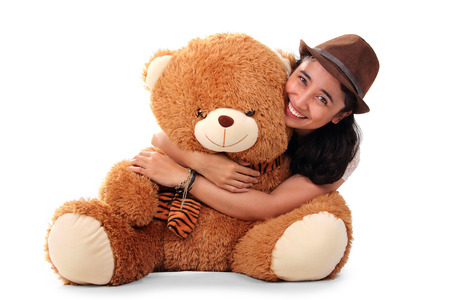 teenage girl happy: Beautiful Asian girl wearing fedora hat, hugging her big brown teddy bear from behind and smiling to camera, isolated on white background Stock Photo