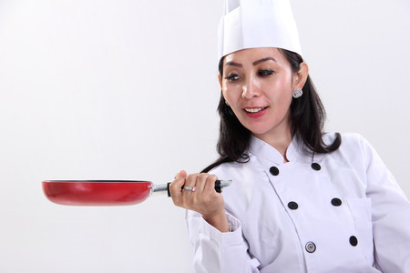 pan asian: Female Asian chef looking at a red frying pan she holds, isolated on white background Stock Photo