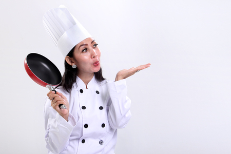 blow: Cheerful female Asian chef blows a kiss to copy space on white background