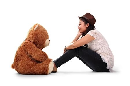 imaginary dialogue: Teenage girl in hipster style sits facing her brown teddy bear on the floor, as if theyre having a conversation, isolated on white background Stock Photo