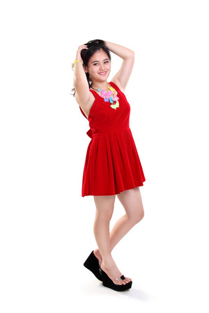 teenage girl dress: Sensual pose of smiling Asian teenage girl in red dress standing, full body portrait isolated on white background