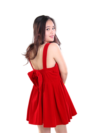 back shot: Back shot portrait of beautiful young Asian lady in cute red dress turning her face toward camera, isolated on white background