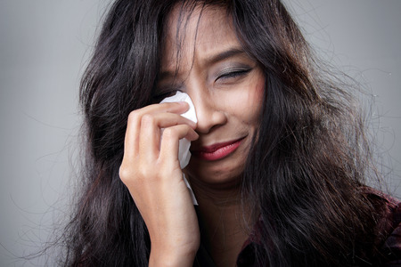 heartbreak issues: Close up portrait of young Asian woman cries in despair and wipes the tears in her eyes, over grey background Stock Photo