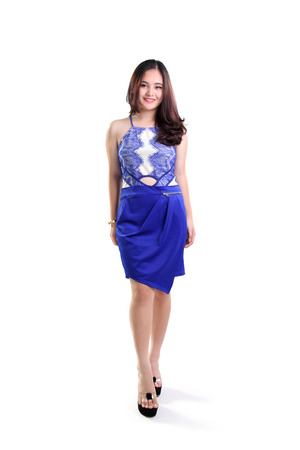 teen beach: Beautiful smiling Asian female fashion model walking in a trendy blue dress, full length shot isolated on white background Stock Photo