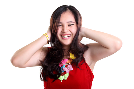 expressive face: Expressive face of beautiful cheerful Asian girl feeling good, smiling brightly with both hands covering her ears, isolated on white background