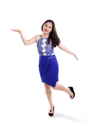 casual wear: Full length shot of happy girl in blue dress standing with playful body language, isolated on white background Stock Photo