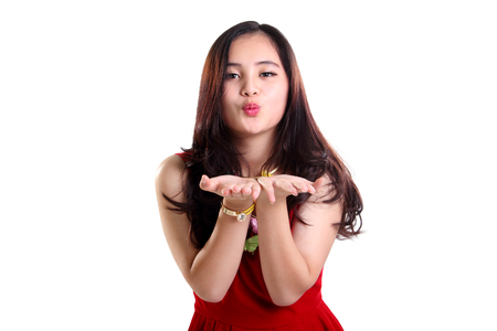 Lovely young Asian lady in red dress blowing romantic kiss to camera, isolated on white background