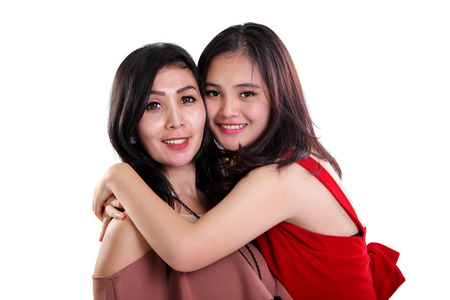 Lovely Asian mother and daughter embracing and smiling to camera, isolated on white background Archivio Fotografico