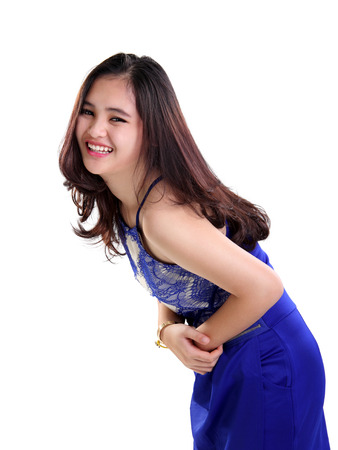 cheerfully: Portrait of happy Asian teenage girl in bright blue dress laughing cheerfully, isolated on white background Stock Photo
