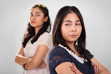 cynical: Conceptual image of two Asian girl in conflict, standing against each other with cynical looks Stock Photo