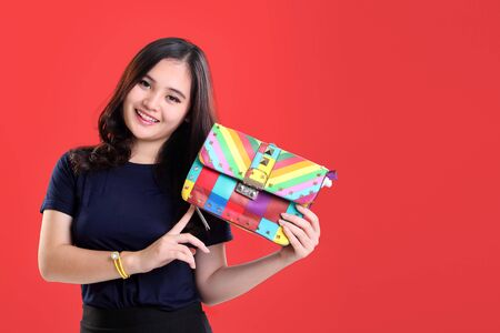 happy asian people: Beautiful young Asian female model smiling while showing a colorful fashionable bag in her hands, with copy space ready to use for design