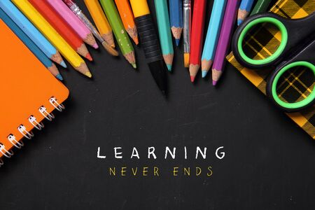ends: Learning never ends. Inspirational design with school supplies on top of blackboard texture