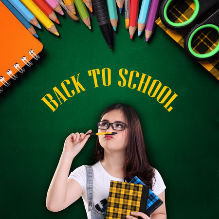 stationery needs: Smart thoughtful female student thinking about back to school, colorful supplies over green chalkboard background