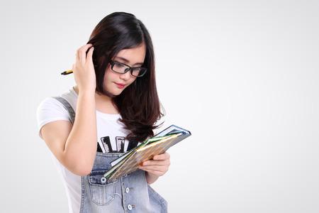 cabeza de mujer: Estudiante confuso hembra rascándose la cabeza mientras mantiene algunos libros, aislado en fondo blanco