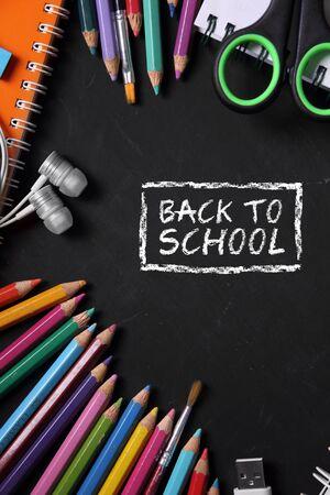 semester: Back to school. Colorful school supplies over black board background design