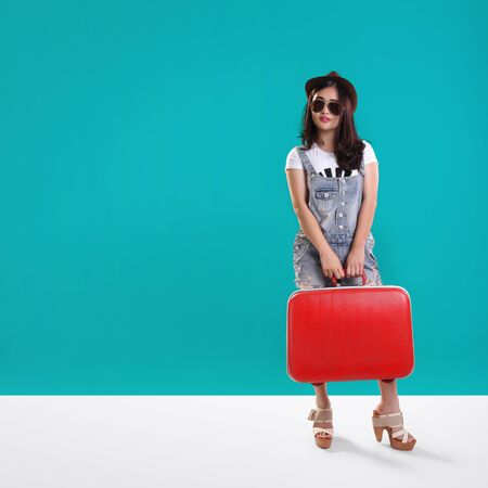 casual wear: Cool hipster traveler girl standing with a vintage red suitcase, over turquoise background for copy space