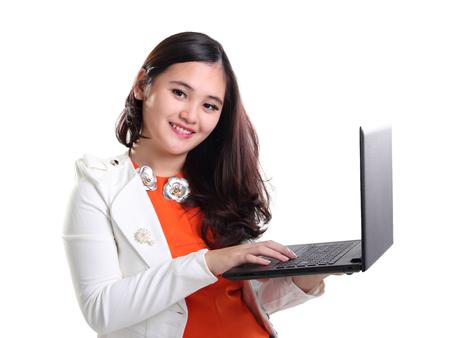 Pretty Asian girl in business suit holding a laptop and smiling at camera, isolated on white background