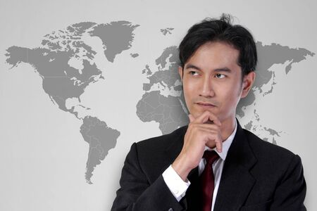 world thinking: Handsome young Asian business expert thinking, over world map illustration on the background. Globalization concept Stock Photo