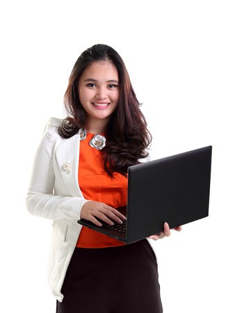 Portrait of friendly female professional worker smiling while carrying a laptop, isolated on white background Reklamní fotografie