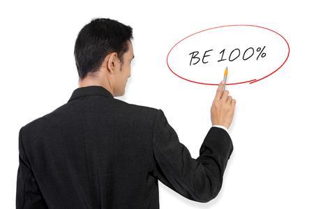 彼のペンでホワイト ボードに「100% になる」手書きテキストを指してビジネスマン 写真素材