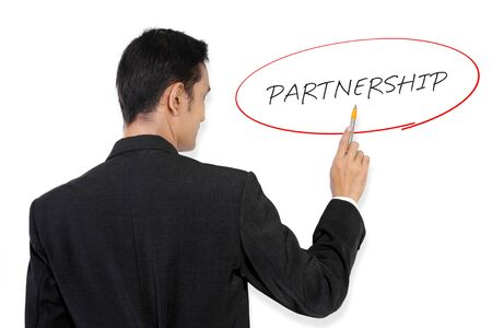 affiliation: Businessman pointing at Partnership handwritten text on white board with his pen Stock Photo