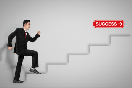 career plan: Young Asian businessman steps on ladder to success