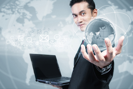 operating system: Modern Asian businessman showing digital earth in his hand. Conceptual design of internet multimedia & technology Stock Photo