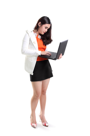 computer isolated: Full length portrait of young Asian businesswoman using laptop standing, isolated on white background Stock Photo