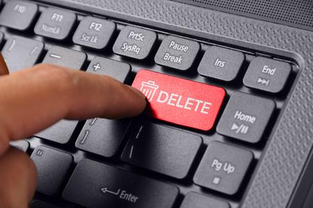 Gebaar van een handvinger drukken DELETE op een laptop toetsenbord
