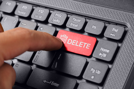 operating key: Gesture of a hand finger pressing DELETE on a laptop keyboard