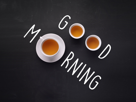 rise: Good Morning. Tea cups composed with written text on blackboard Stock Photo