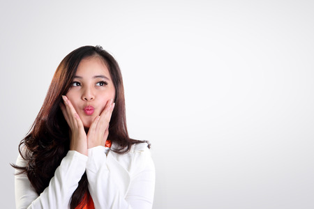 fanatic studio: Young Asian woman making cute excited face while admiring something at copy space sideways on white background Stock Photo