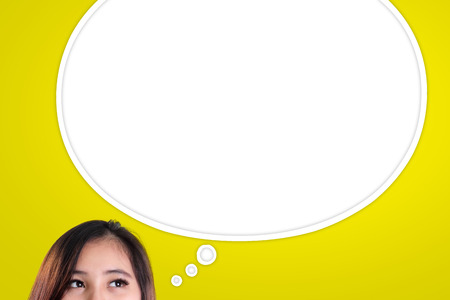 people looking up: Eyes of Asian woman looking at empty thought bubble, over yellow background Stock Photo