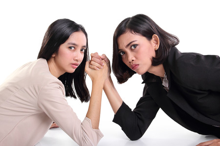 Two young Asian businesswomen with arms wrestled looking at camera aggressively, isolated on white background