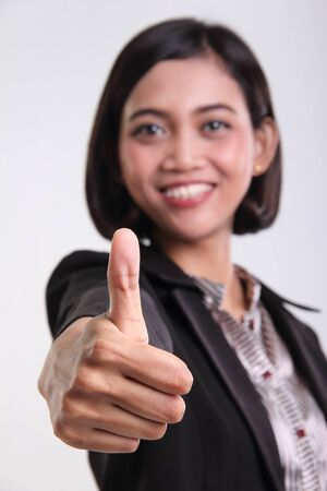 thumbup: Thumb up of an attractive Asian corporate woman, close up portrait against isolated background